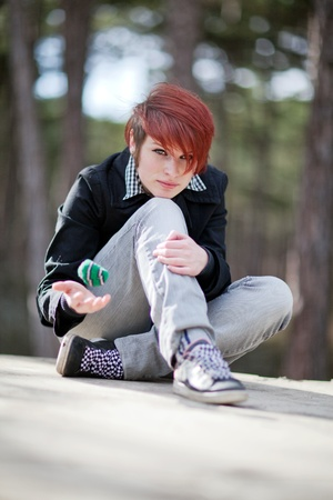 An young girl, wearing jeans and jacket,  is sitting and playing with knitted ball in the forest photo