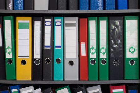 Row of file folders on a shelf, different colors and sizes Stock Photo - 965152