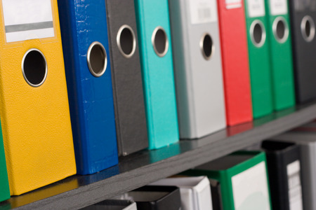 Row of file folders on a shelf, different colors and sizes. Shallow depth of field, the nearest yellow folder is in focus Stock Photo - 1685630