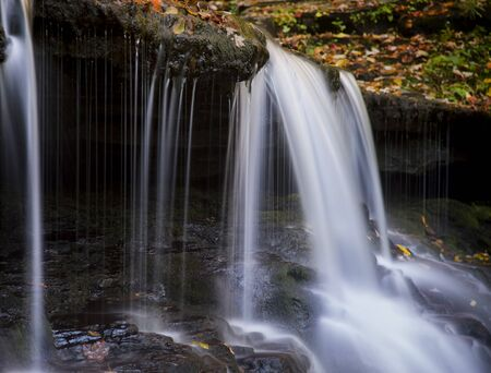A small waterfall surrounded by bright fall colors. Stock Photo