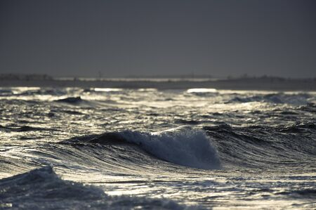 A dramatic stormy sea as the sun shines on a crashing wave.