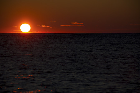 A red sun sits on the horizon of the Atlantic Ocean at first light.