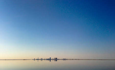 appears: A city appears to be floating on the water on a very calm day.