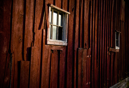 old red barn: An old red barn window with a spotlight of sun Stock Photo