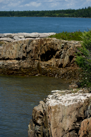 rugged: A rocky outcrop juts out into the ocean along a rugged coastline. Stock Photo