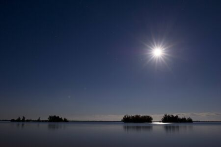 nightscape: A nightscape of a calm river with a bright moon over some small islands. Stock Photo