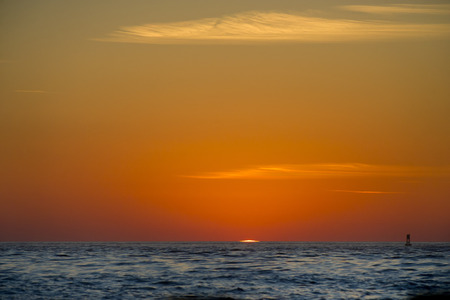 sliver: A thin sliver of the sun shows over the horizon as the beginning of a new day starts. Stock Photo