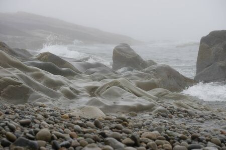 A smoothly worn rocky coastline with crashing waves and small pebbles on a foggy day.