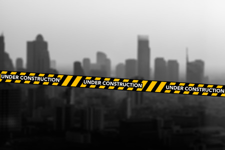 out of danger: Caution and danger ribbon strip tape with citi out of focus Stock Photo