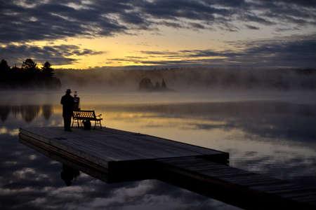 Artist painting during sunrise on Algonquin lake Stock Photo
