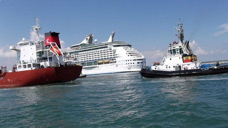 ravenna: pilot accompanies a tanker in port on the background of a cruise ship