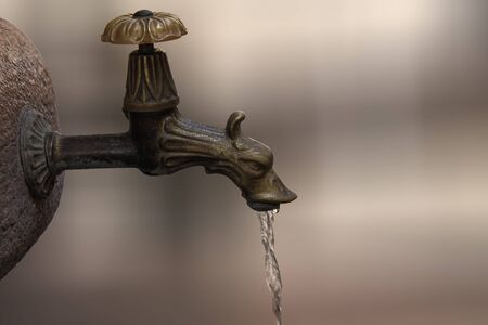 vintage, antique faucet from which water flowing Reklamní fotografie