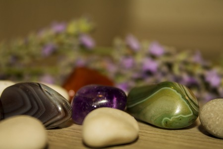 green gemstone: semi-precious stones on a wooden surface, close-up Stock Photo