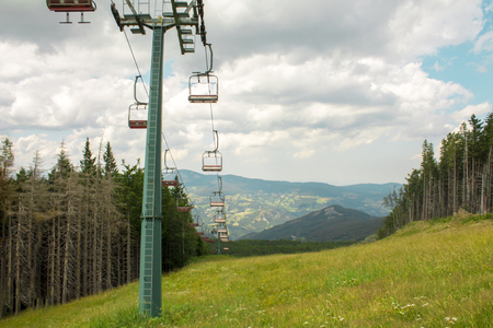 Chairlift ski lift in European Alps. Transporting hikers in summer season.