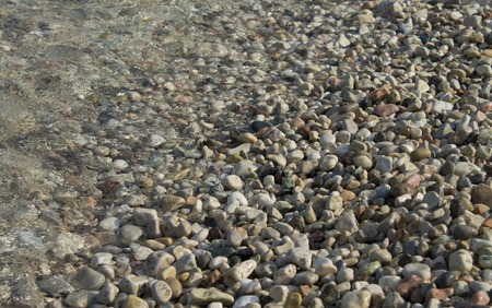 Pebbles in crystal clear lake water close up