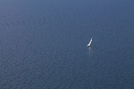 Alone Sailing boat in the windy summerday on lake Garda Italy