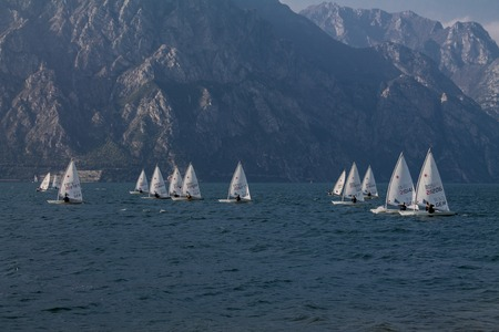 Sailing boat in the windy summerday on lake Garda Italy.Childrens sports competitions