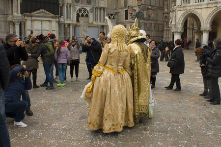 Photographers take pictures of a couple in the carnival costumes in Venice Italy Editorial