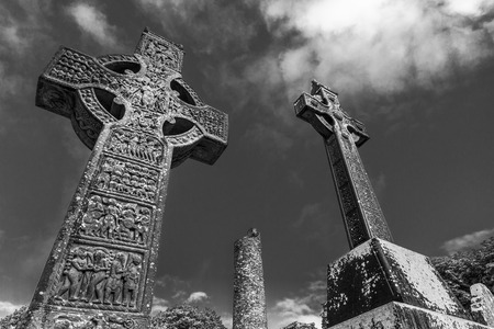 Celtic crosses contrasted in black and white showing the sky with clouds Archivio Fotografico - 112969001