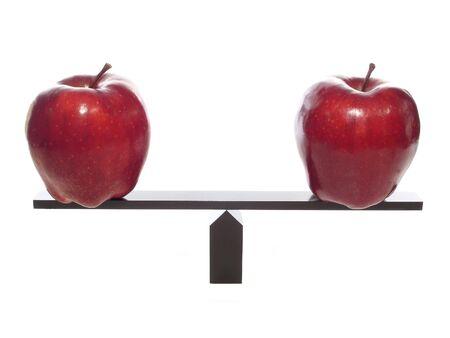 Al comparar manzanas a las manzanas en una balanza, aislados en blanco  Foto de archivo