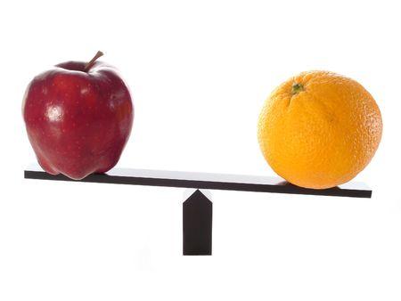 Vergleichen der Äpfel mit Orangen auf einem Schwebebalken Standard-Bild