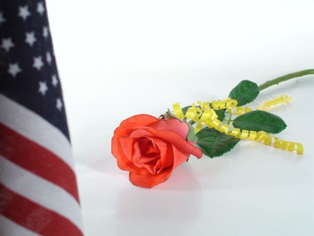 Red Rose, yellow ribbon symbolic of loved one in the US armed forces, with American flag in the foreground.