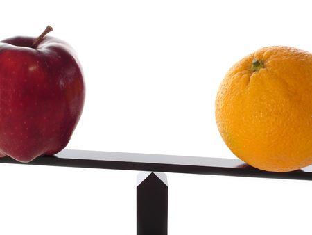Comparando manzanas a las naranjas pesadas en una viga de balance aislada en el primer blanco. Foto de archivo
