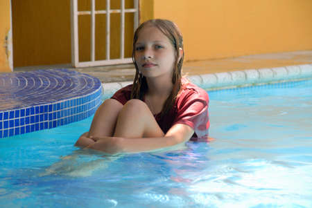 Young girl sitting in the pool on a step half in water and half out.