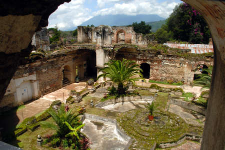Fountain courtyard of San Francisco Church in Antigua Guatemala volcano Pacaya in background