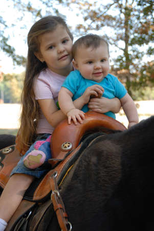 Two happy children riding a horse outdoors.