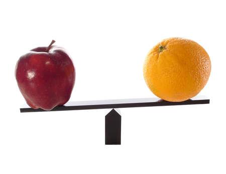 Metapher für den Vergleich Äpfel mit Orangen auf einem Waagebalken isoliert auf weiß und die Orangen sind nicht so schwer oder leicht.