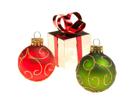 Christmas tree ornaments isolated on white background shiny gift box in distance slight blur intentional. Stock Photo - 3940708