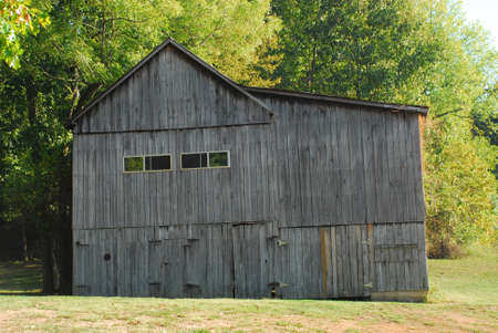 Tobacco barn in the farmland surrounded by trees. Stock Photo