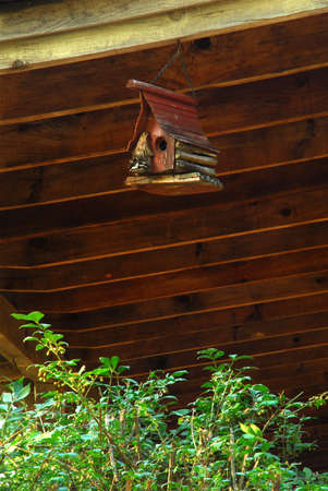 man made: Bird house on the end of the porch. Man made cottage that is a shelter for birds.