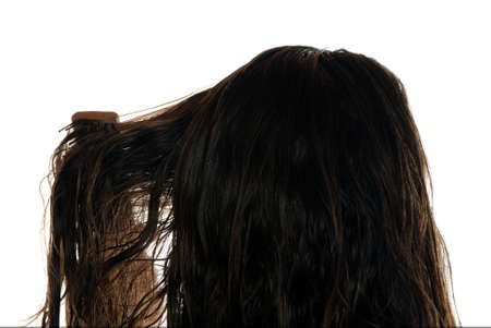 Close up rear view of young woman brushing wet hair