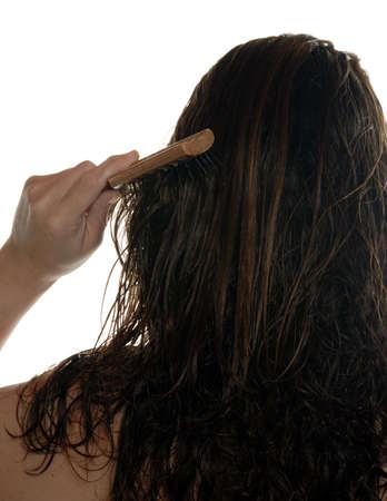 Head only rear view of young woman brushing wet hair