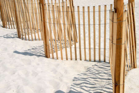 Picket fence on white sand beach in Panama City Florida USA. Used to protect and conserve the dune grass on the beach.  photo