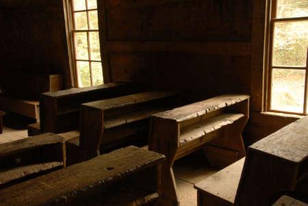 school house: Escritorios de aula cosecha dentro de una casa de escuela del pa�s de una habitaci�n. Mirando desde la espalda al frente.