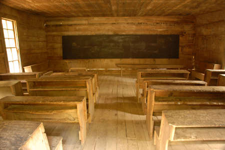 Vintage classroom desks inside a one room country school house. Looking from back to front. photo