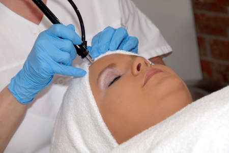 hair treatment: Laser skincare treatment Laser hair removal being preformed on forehead of woman wrapped in a towel.