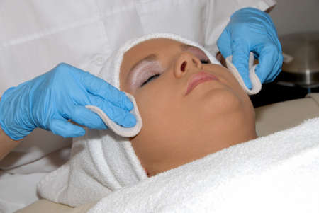chemical peels: Skincare facial treatment at day spa being preformed on face of woman wrapped in a towel.