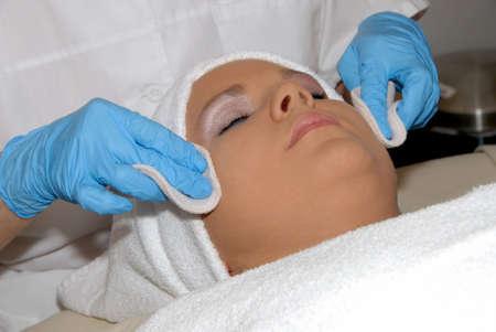 masajes faciales: Tratamiento facial de cuidados en spa de d�a siendo preformada en cara de mujer envuelta en una toalla.