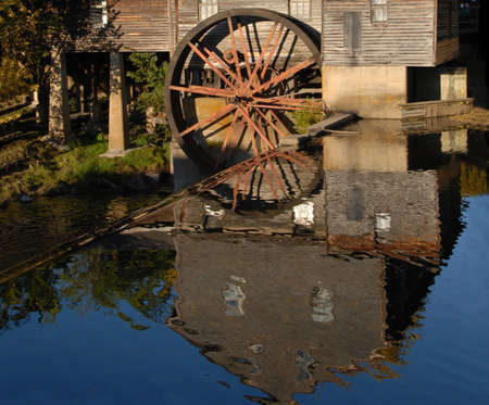 gristmill: Reflection in the water of an old grist mill. The water wheel is standing still and no longer in use. A true reflection of time gone past. A gristmill or grist mill is a building in which grain is ground into flour. Stock Photo