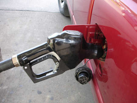 Gas pump nozzle filling up vehicle with gas. Stock Photo