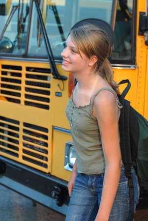 Happy teenage girl walking around a school  bus with backpack full of books.
