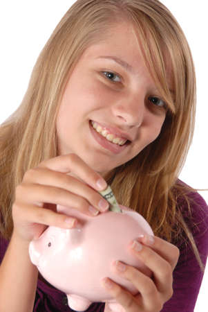 financal: Teenage girl smiles while she is saving her money by putting it into a pink piggy bank she is holding in front of her. Studio shoot wearing a purple blouse.