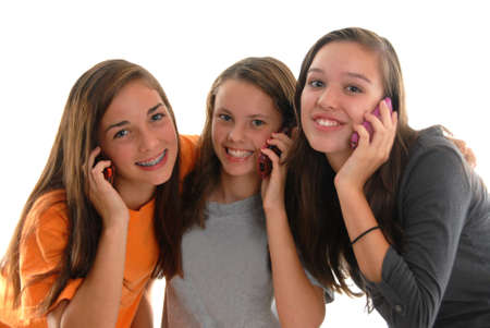 Three happy teenage girls smiling while talking on cell phones. Studio with white background.  Zdjęcie Seryjne