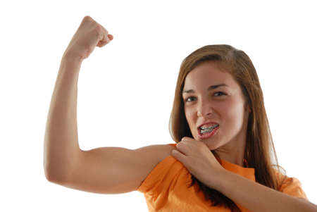 bicep: Teenage physically fit confident girl making an arm muscle gritting teeth as if to show how tough she is and meaning bring it on. Studio white background. Stock Photo