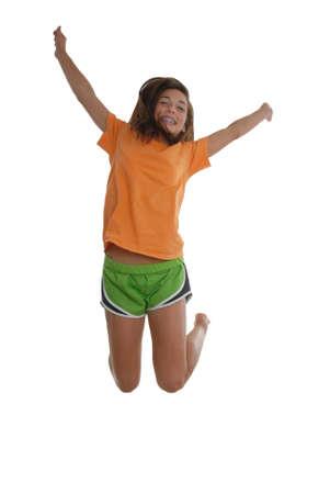 knees bent: Allegra ragazza adolescente felice saltare in aria con braccia e piedi dietro le ginocchia piegate la testa arcuato all'indietro indossando t-shirt e pantaloncini.