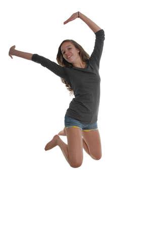knees bent: Allegra ragazza felice graziosa adolescente saltare in aria con braccia e piedi dietro le ginocchia piegate la testa arcuato all'indietro indossando t-shirt e pantaloncini.